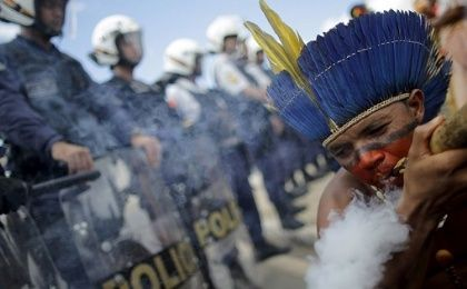 A man smokes a pipe in front of a row of riot police officers outside the Planalto Palace in Brasilia.