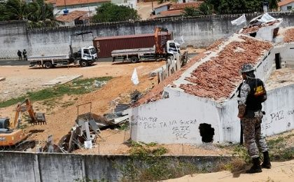 Workers place a container to separate two factions of drug gangs during an uprising at Alcacuz prison in Natal.