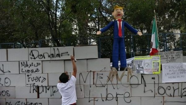 An activist works on a symbolic wall built by protesters outside the US embassy in Mexico City, Mexico.