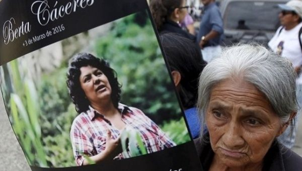 A woman with a poster of slain environmental activist Berta Caceres.