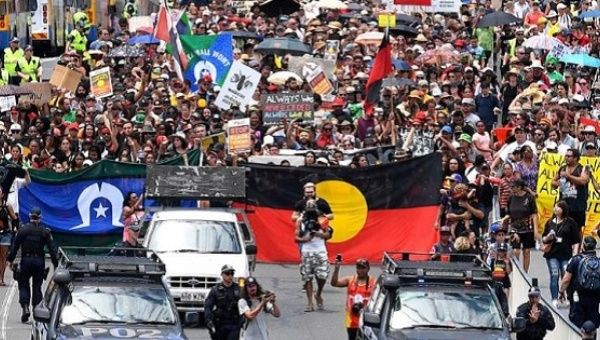 Police escort people joining a march with Aboriginal protesters on Australia Day in central Brisbane, Australia.