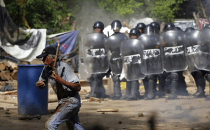 An injured protester flees as riot police use tear gas and batons to disperse a protest against the Tambor mine, Guatemala, May 23, 2014.