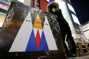 A Japanese graffiti artist known as 281 Antinuke poses with his sticker art depicting Donald Trump in Tokyo's Shibuya shopping district, Jan. 27, 2017.
