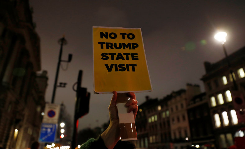 A demonstrator holds a placard during a protest against U.S. President Donald Trump