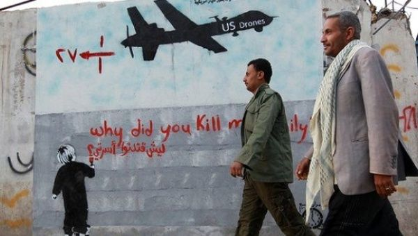 "Yemeni men walk past a mural depicting a U.S. drone, which reads, ""Why did you kill my family,"" in the capital of Sanaa."