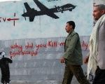 Yemeni men walk past a mural depicting a US drone and reading 'Why did you kill my family,' in the capital, Sanaa.