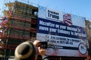 A man takes a picture of a giant banner on a building congratulating U.S. President-elect Donald Trump in Jerusalem.