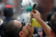 Demonstrator in Bogota, Colombia, smokes marijuana in defiance of new police law.