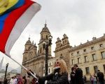 People demonstrate on the street as Colombia's President Juan Manuel Santos and Marxist FARC rebel leader Rodrigo Londono, known as Timochenko, sign a new peace accord in Bogota, Colombia, Nov. 24, 2016.