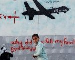 Yemeni men walk past a mural depicting a U.S. drone, which reads,