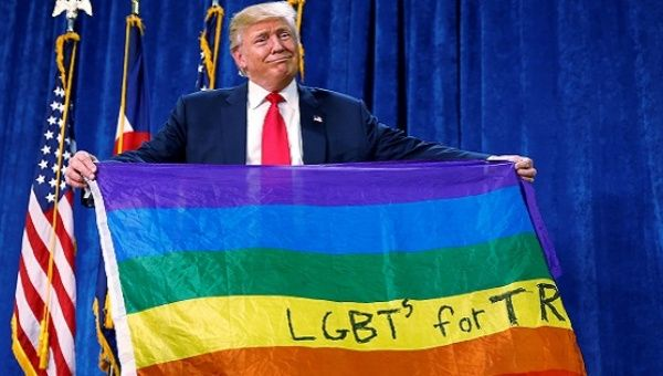 "Donald Trump holds up a rainbow flag with ""LGBTs for TRUMP"" written on it at a campaign rally in Greeley, Colorado, October 2016."