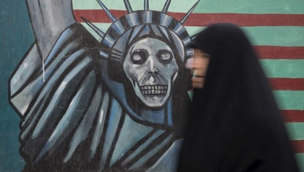 An Iranian woman walks past an anti-U.S. mural painted on the wall of the former U.S. Embassy in Tehran.