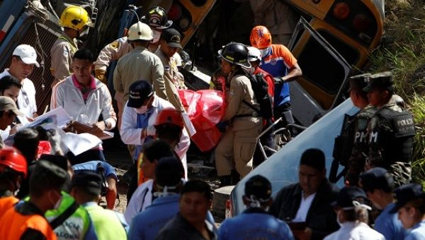 Rescue workers and members of the red cross carry a body after a crash between a bus and a truck on the outskirts of Tegucigalpa, Honduras, Feb. 5, 2017.