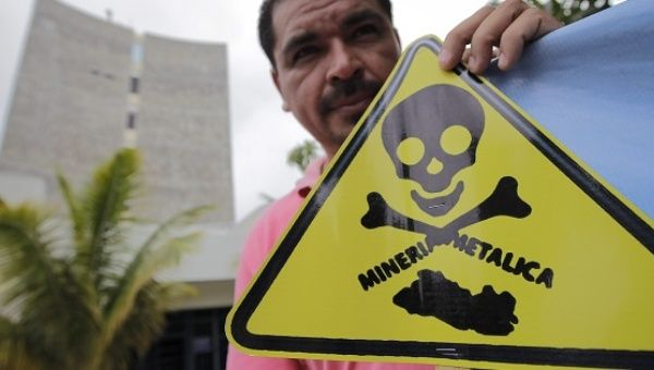 An demonstrator holds a sign condemning the toxicity of metals mining in El Salvador after an anti-mining coalition presented a proposal to block mining in 2013.