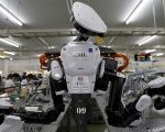 A humanoid robot works side by side with employees in the assembly line at a factory of Glory Ltd., in Kazo, north of Tokyo.