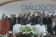 Lead negotiators from the ELN and the Colombian government shake hands.