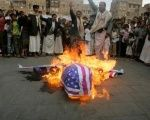Protesters loyal to the Shi'ite al-Houthi rebel group burn an effigy of a U.S. aircraft during a demonstration to protest against what they say is U.S. interference.