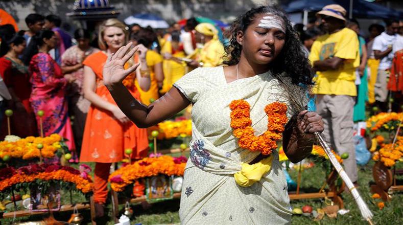 """Los devotos caminan durante la ceremonia llevando su """"Kavadi"""" de flores hacia el Templo Tamil Shree donde realizarán la ceremonia."""