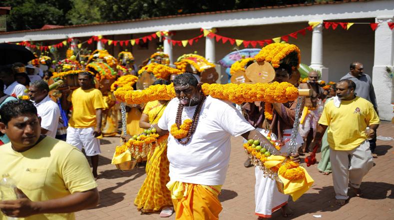 Los fieles caminan hacia el templo durante la ceremonia de Kavadi con los pernos que perforan sus lenguas y piel.