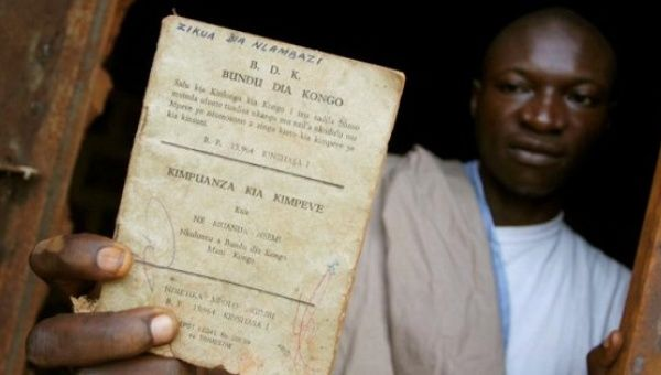 A resident holds up a Bundu dia Kongo manifesto left behind after a police crackdown on the religious and political movement in Matadi in 2008.