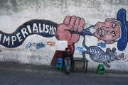 A man sits in front of a mural in Caracas, Venezuela