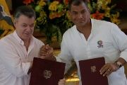 Colombia's President Juan Manuel Santos and his Ecuadorean counterpart Rafael Correa pose with documents after signing a bilateral agreement.