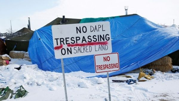 "A modified ""No Trespassing"" sign is seen in the opposition camp against the Dakota Access oil pipeline near Cannon Ball."