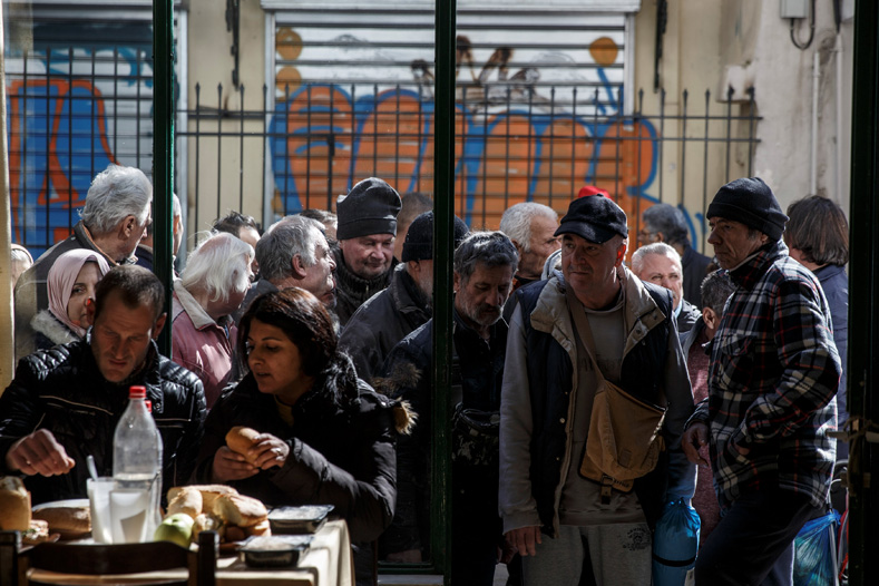 People line up as they wait to enter a soup kitchen run by the Orthodox church in Athens, Greece, Feb. 15, 2017.