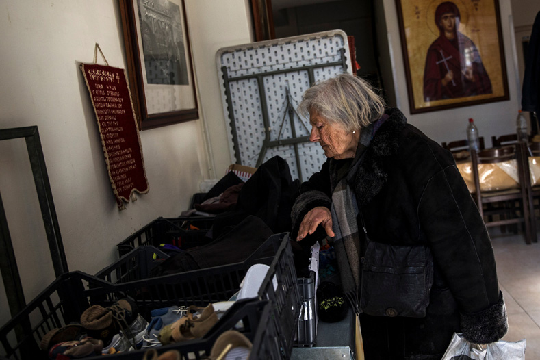 An elderly woman searches through donated clothes at a soup kitchen run by the Orthodox church in Athens, Greece, Feb. 15, 2017.