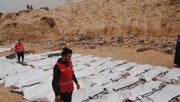 Red Crescent workers inspect the washed up bodies of the refugees on a shore in western Libya.