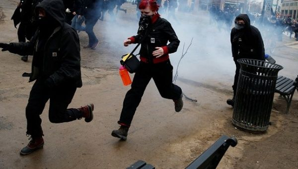 Activists set out running after being hit by a stun grenade while protesting against U.S. President Donald Trump.