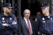 Former IMF chief Rodrigo Rato (C) walks between police officers as he leaves his office in Madrid, April 17, 2015.