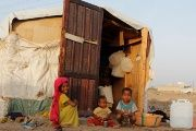 Children sit next to their hut at a makeshift camp for internally displaced people in al-Jarahi south of the Red Sea port city of Houdieda, Yemen.