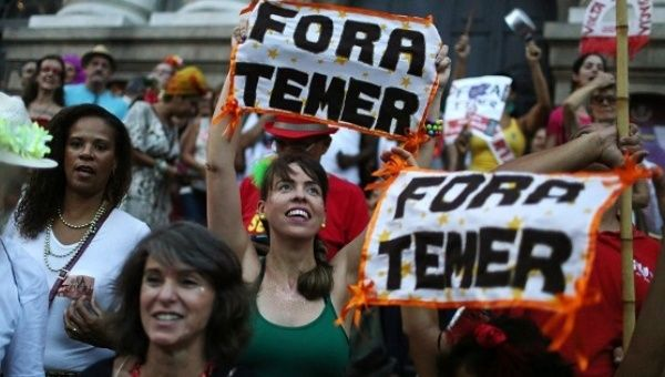 "Brazilians protest with signs saying ""Fora Temer"" during carnival festivities in Rio de Janeiro."