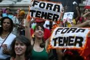 Brazilians protest with signs saying