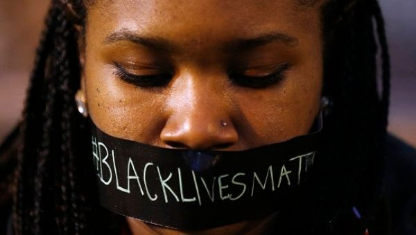 A demonstrator covers her mouth with the #BlackLivesMatter slogan to protest police brutality after the police killing of Michael Brown in Ferguson, Missouri.