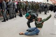 An Israeli border policeman removes a pro-settlement activist from a settlement in the occupied West Bank.