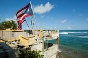 Puerto Rico and U.S. flags flutter on a building that once belonged to a restaurant, in San Juan, March 11, 2014.