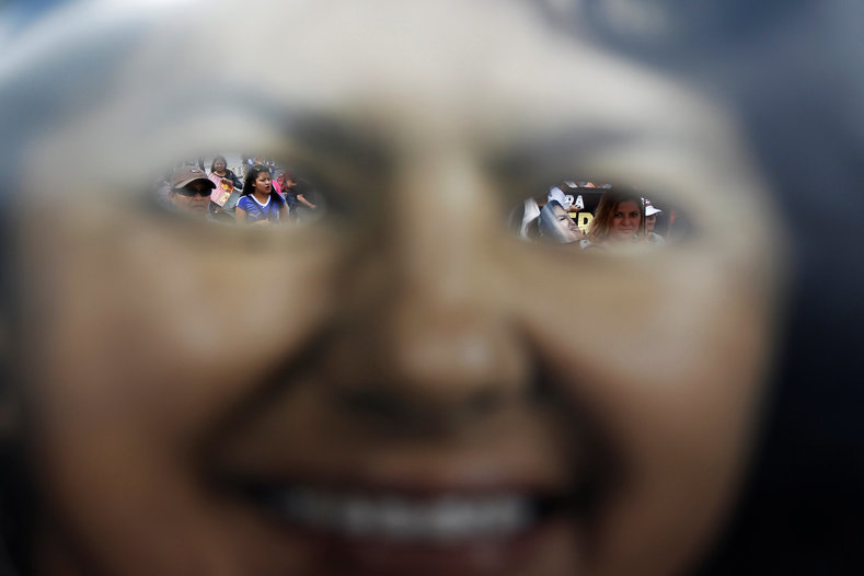 Protesters are seen through the eyeholes of a mask of slain environmental rights activist Berta Caceres during a march to mark the first anniversary of her murder, in Tegucigalpa.