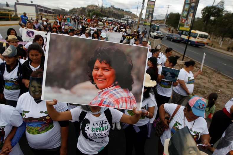 A protester holds up a picture of Berta Caceres during a march to demand justice for the murdered activist.