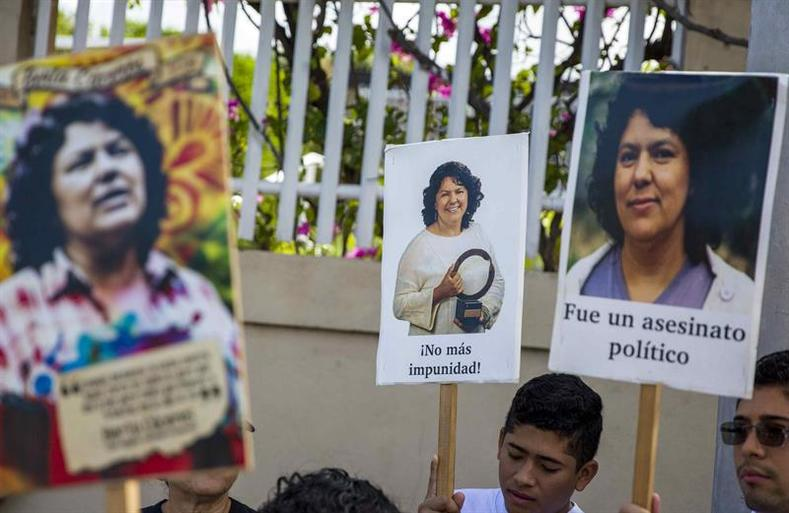 "Protesters hold signs with pictures of Berta Caceres. The signs read ""No more impunity"" and ""It was a political assassination."""