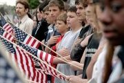 Young people during the pledge of allegiance at a funeral ceremony.