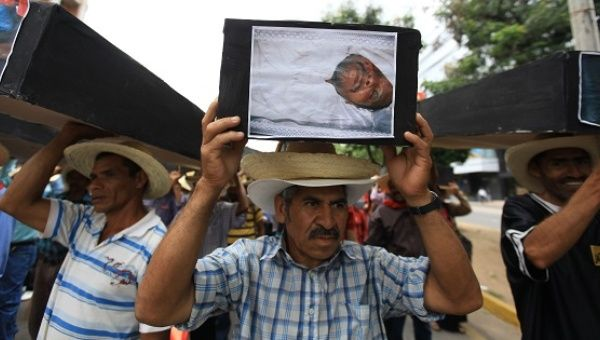Campesinos march with mock coffins with images of victims from the Aguan Valley region during a demonstration in Tegucigalpa, Honduras, Sept. 15, 2012.