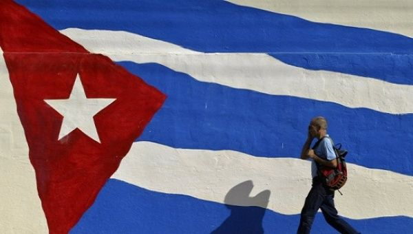 A man walks by a mural of the Cuban flag.