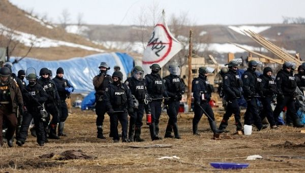 Law enforcement officers advance into the main opposition camp against the Dakota Access oil pipeline near Cannon Ball.
