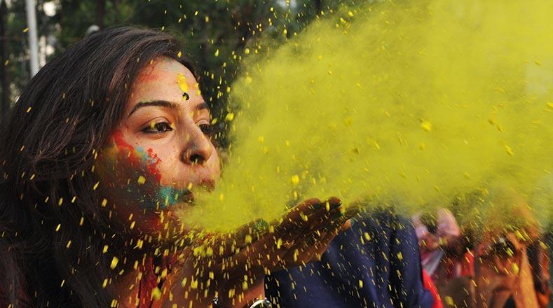 Los asistentes juegan a lanzarse polvos de colores en las calles de la India para rendir culto al dios Vishnú y su avatar Krishna.