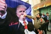 Palestinian demonstrators throw shoes on a poster depicting U.S. President Donald Trump during a protest in the West Bank city of Hebron, Feb. 24, 2017.