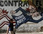 A woman walks past anti-U.S. imperialism graffiti in Caracas. March 9, 2015