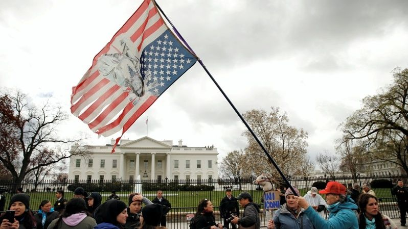 An Indigenous activist waves an upside down U.S. flag with an image of historic Native American leader Sitting Bull on it during a protest march and rally in opposition to the Dakota Access and Keystone XL pipelines in front of the White House.