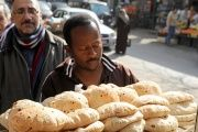 Men queue to buy bread at a bakery in Cairo.